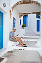 Greece, Amorgos island, young man using a smartphone - GEMF000947
