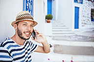 Greece, Amorgos island, young man talking on cell phone - GEMF000950