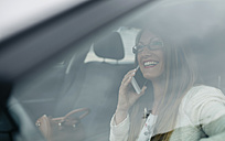 Smiling businesswoman on cell phone in car - DAPF000213