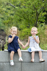 Portrait of two little sisters sitting hand in hand on a wall eating pastries - HAPF000683