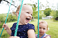 Laughing little girl on a swing with sister in the background - HAPF000689