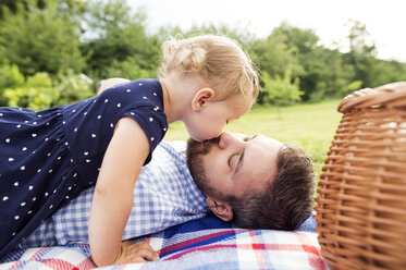 Little girl kissing her father lying on blanket on a meadow - HAPF000704