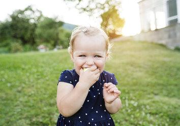 Portrait of little blond girl eating pastry - HAPF000710