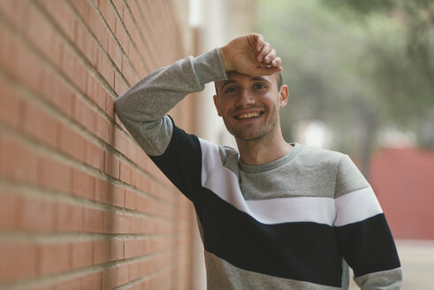 Portrait of smiling man at brick wall - SKCF000157