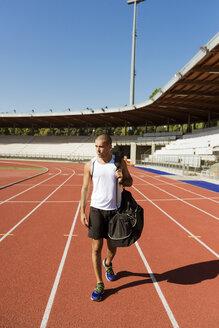 Young sportsman walking on tartan track - FMOF000083