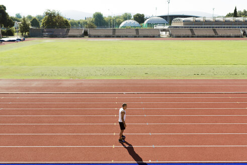 Young sportsman standing on tartan track - FMOF000089