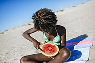 Young woman cutting watermelon on the beach - KIJF000628