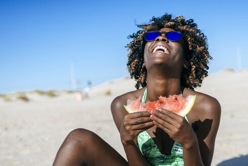 Happy young woman eating watermelon on the beach - KIJF000631
