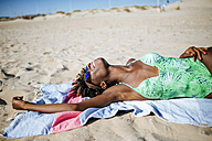 Young woman lying on a towel on the beach - KIJF000640