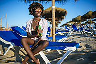 Young woman sitting on the beach drinking beer - KIJF000670