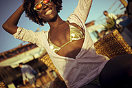 Smiling young woman at a beach bar - KIJF000679