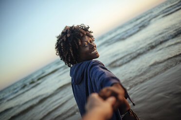 Young woman taking hand of a man on the beach at sunset - KIJF000688