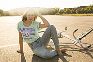 Smiling young woman with bicycle sitting in backlight - TKF000458