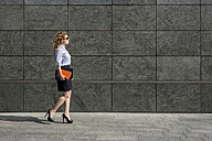 Businesswoman holding book and digital tablet walking outdoors - MAUF000681