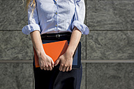 Businesswoman holding book and digital tablet outdoors - MAUF000684