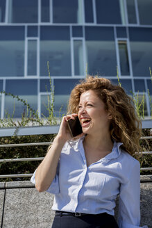Laughing businesswoman on cell phone outdoors - MAUF000687