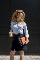 Businesswoman holding coffee to go, book and digital tablet outdoors - MAUF000702