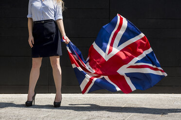 Businesswoman standing outdoors holding British Flag - MAUF000705