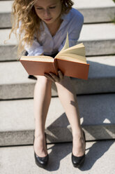 Woman sitting on stairs reading a book - MAUF000708