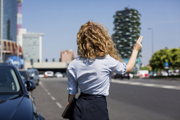 Businesswoman at the roadside hailing a taxi - MAUF000714