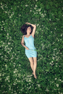 A young woman in a blue dress lying on a summer meadow - MW000106