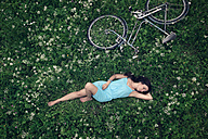 A young woman in a blue dress lying on a summer meadow, beside her, an old vintage bicycle - MW000109
