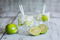 Glasses of infused water with lime and ice cubes - JUNF000544