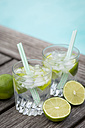 Glasses of infused water with lime and ice cubes - JUNF000547