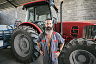 Portrait of confident mechanic at tractor - JASF001062