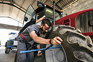 Mechanic changing tractor tyre - JASF001065