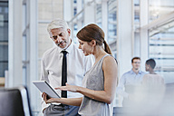 Businessman and businesswoman with digital tablet - RORF000225
