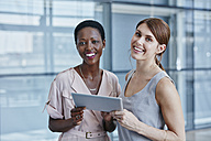 Two businesswomen with digital tablet - RORF000231
