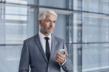 Confident businessman holding cell phone - RORF000237