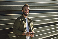 Portrait of smiling man with cell phone standing in front of facade - RAEF001344