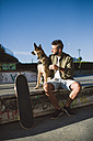 Skateboarder with his dog in a skatepark - RAEF001347