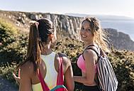 Spain, Asturias, two sportswomen talking, on the coast - MGOF002169
