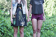 Two fashionable female friends standing hand in hand, partial view - MOMF000003