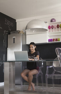 Young woman sitting at table in the kitchen working with laptop - MOMF000018