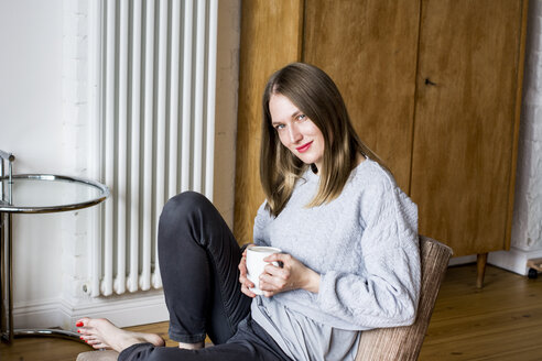 Smiling woman with coffee mug sitting on chair at home - LMF000582