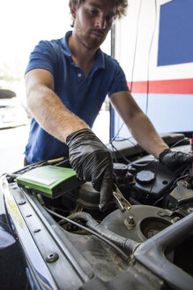 Mechanic placing a battery clip in a car - ABZF000940