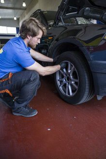 Mechanic examining the wheel of a car - ABZF000943