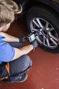Mechanic fixing a car wheel in a workshop - ABZF000946