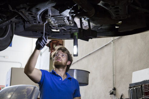 Mechanic fixing suspended car in his workshop - ABZF000955
