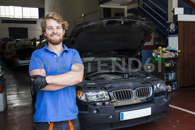 Confident mechanic standing in his car workshop with arms crossed - ABZF000967