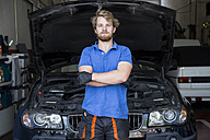 Mechanic standing in his car workshop with arms crossed - ABZF000970