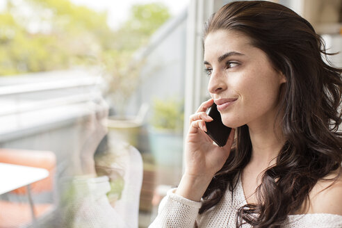 Smiling young woman on cell phone looking out of window - PESF000265
