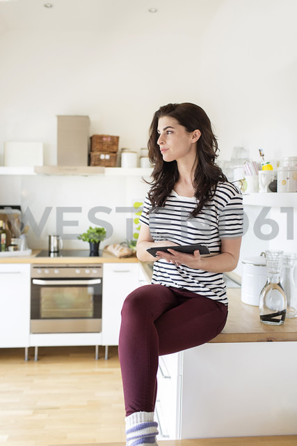 Young woman in kitchen using digital tablet - PESF000271