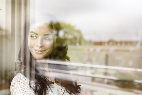 Smiling young woman looking out of window - PESF000277