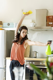 Young woman in kitchen cleaning and listening to music - PESF000280