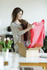 Smiling woman at home unpacking parcel with garment - PESF000301